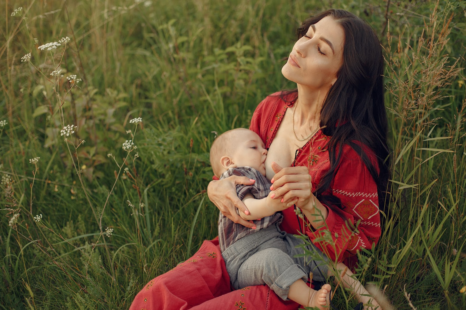 Mother with cute daughter. Mom breastfeeding her little son.