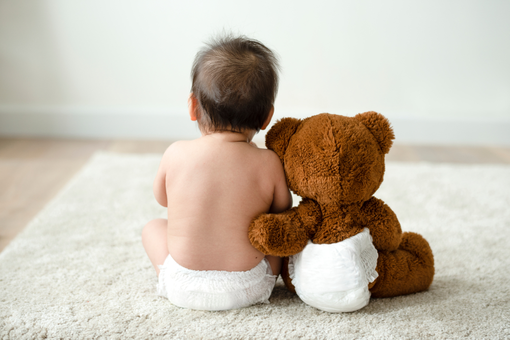 baby and teddy in single use diapers