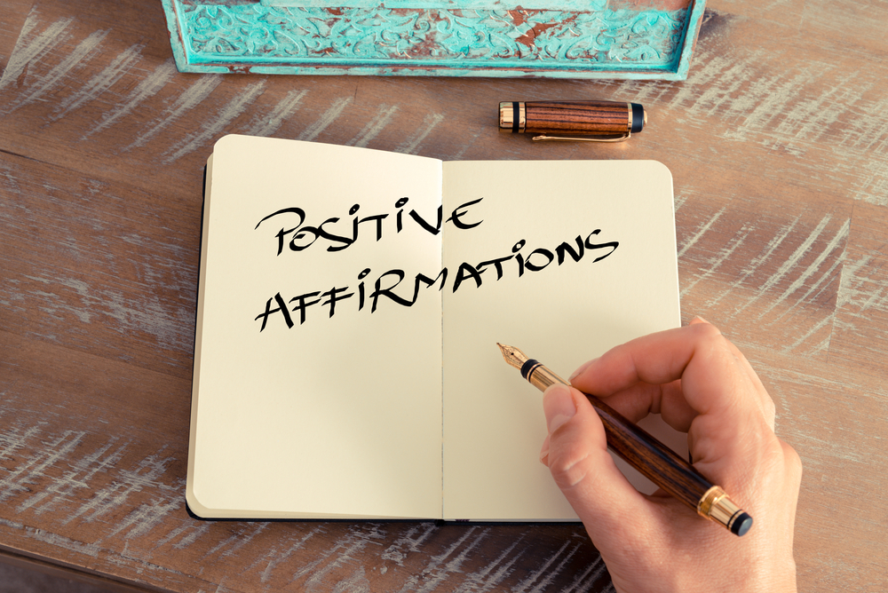 """Writing """"positive affirmations"""" on a note-book"""